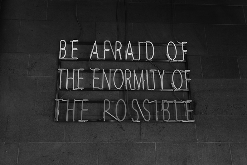 Illuminated sign: Be afraid of the enormity of the possible.